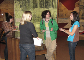 four students take notes and observe the exhibits in the park's Visitor Center