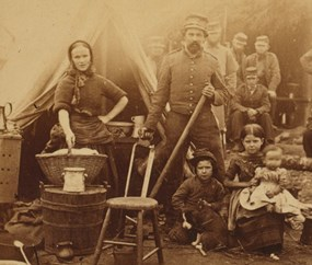 historic image of a Civil War-era washerwoman, man, and two children outside a tent
