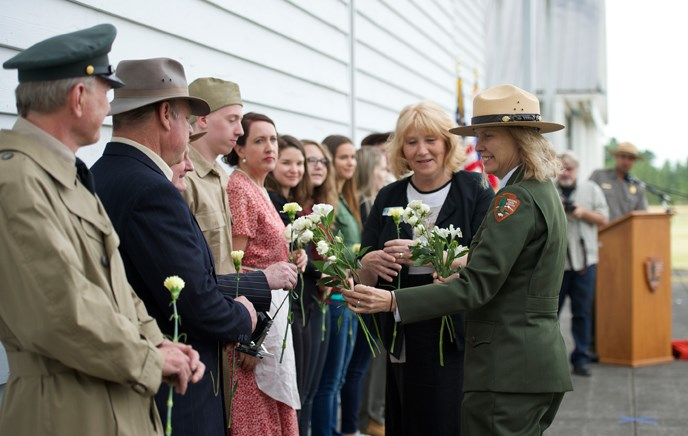 Photo of park superintendent Tracy Fortmann handing flowers to costumed actors who participated in a theatrical performance about the history of Pearson Field.