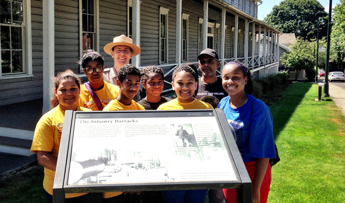 Image of park ranger and participants in NAACP Rites of Passage Academy posing beside a wayside exhibit and historic building.