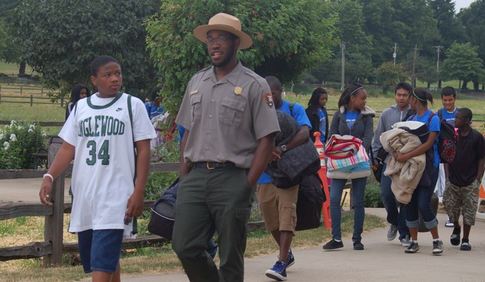 Image of ranger walking on a trail and speaking to students.