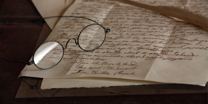 photo of a reproduction pair of glasses sitting atop a handwritten letter and a feather quill.
