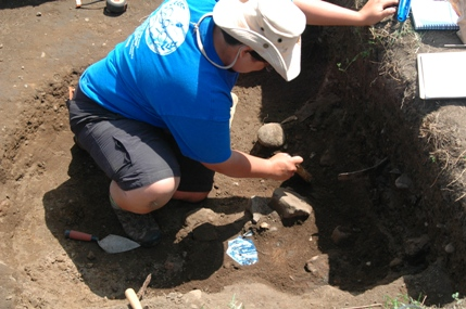 Field School student excavating a trash pit