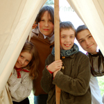 Four children in historic costume look out from the inside of a fur trade-era tent.
