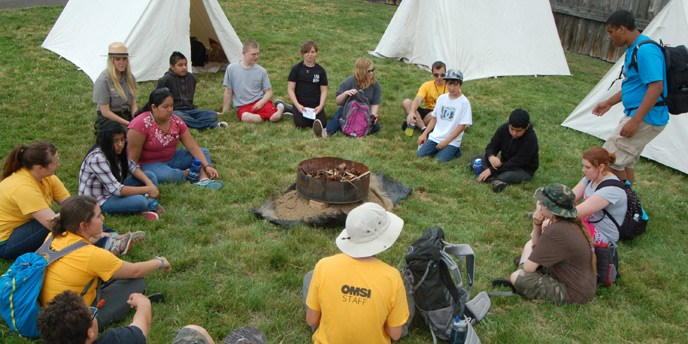 Campers sit on a circle in the grass outside with Park Rangers and OMSI instructors, with tents in the background.