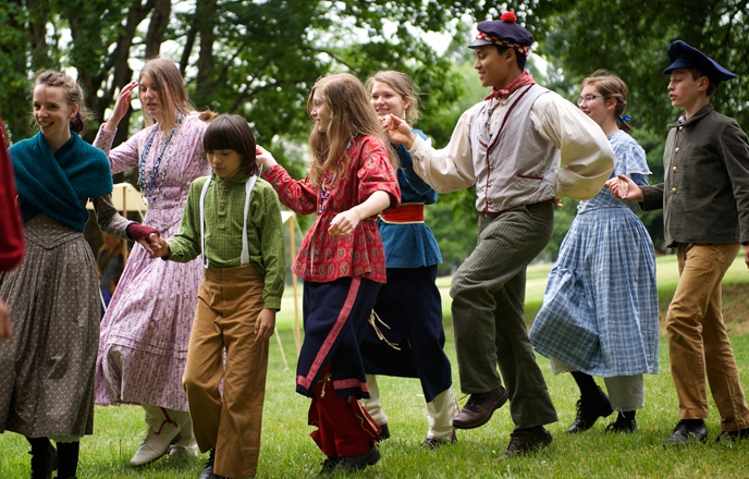 Photo of Living History School participants dancing for the public at a park special event.