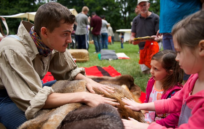 A young engage class member introduces young visitors to furs at an outdoor park event.