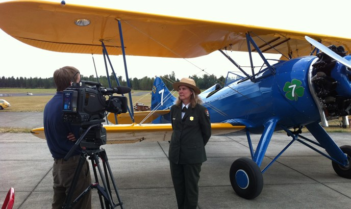Superintendent Tracy Fortmann speaks to the media in front of a historic biplane at Pearson Air Museum.