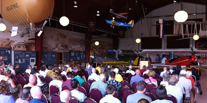 Superintendent Tracy Fortmann speaks to a seated group inside Pearson Air Museum.