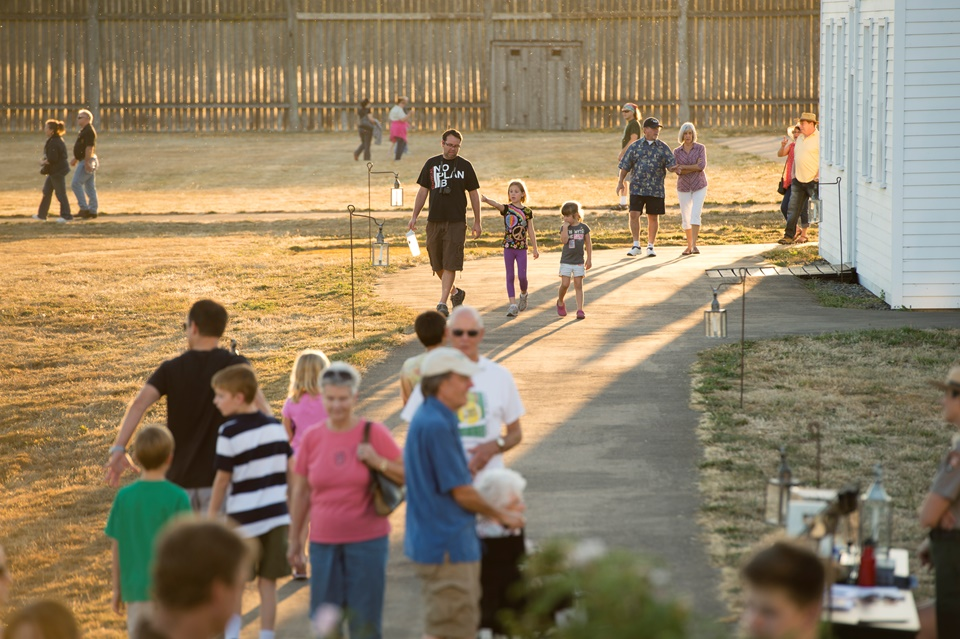 Inside Fort Vancouver at twilight, groups of people walk along paths
