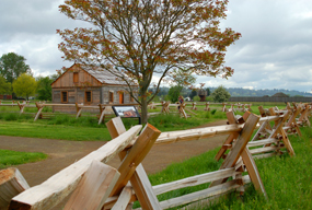 View of the fence line and replica of Village House 2