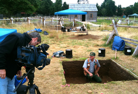 Dr. Douglas Wilson describes an archaeology dig for news cameras while sitting in an excavation pit in the Fort Vancouver Village.