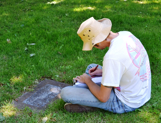 Student sitting and recording information in a notebook from a grave marker.