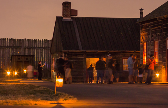Image of visitors enjoying the campfires & candlelight special event by lantern light in 2012.