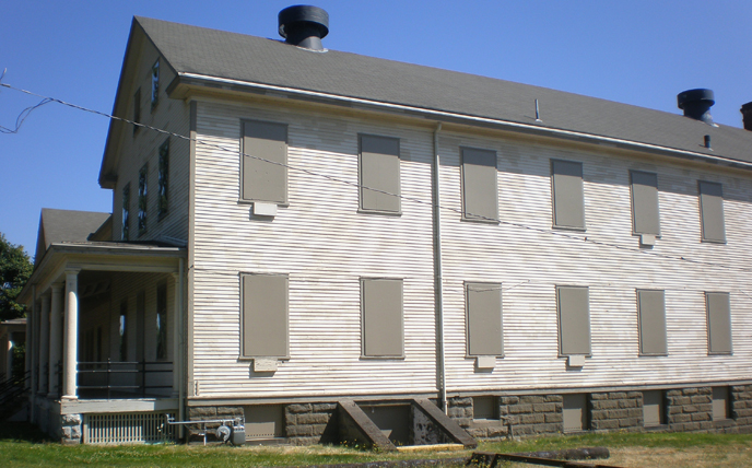 View of the west side of one of the large barracks buildings that frames the south side of the historic Parade Ground at Fort Vancouver NHS
