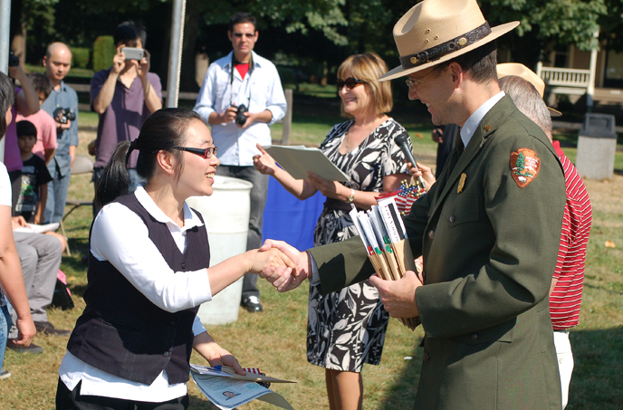 Image of Chief Ranger Shine greeting a new U.S. citizen at the annual Citizenship Ceremony at the Bandstand at Fort Vancouver NHS.