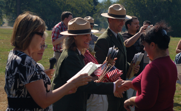 Image of dignitaries welcoming new U.S. citizens as part of the annual Citizenship Ceremony at the bandstand at Fort Vancouver NHS.