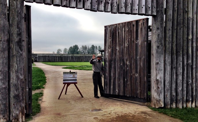 Image showing park ranger opening the main stockade gate at Fort Vancouver NHS and waving to welcome returning visitors.