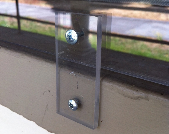 Detailed photo of plexiglass window covering and screw used to preserve a historic window at East Vancouver Barracks