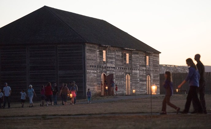 The reconstructed Fur Store at twilight, with candle lanterns outside and people walking around nearby.
