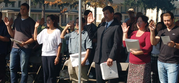 New candidates for citizenship raising their right hands under an awning, being sworn in at Fort Vancouver's Parade Ground.