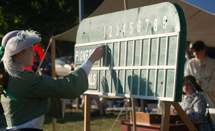 Image of costumed woman adjusting the scoreboard at an 1860s vintage base ball game.