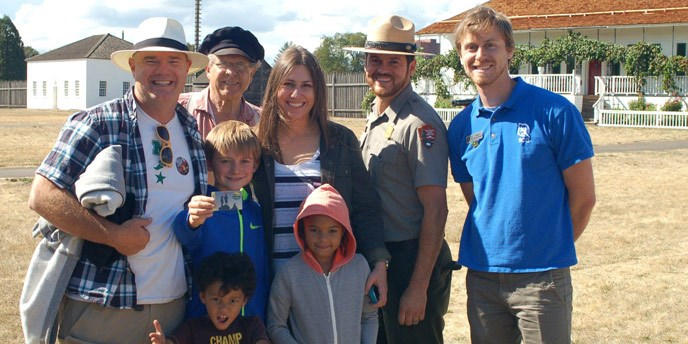 A family shows its new 4th grade park pass while posing with NPS staff in uniform and costume.