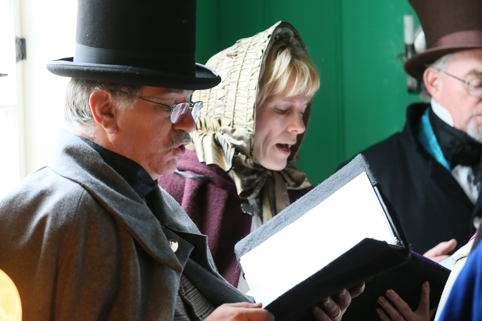 Three carolers in period clothing sing Christmas carols from a book.