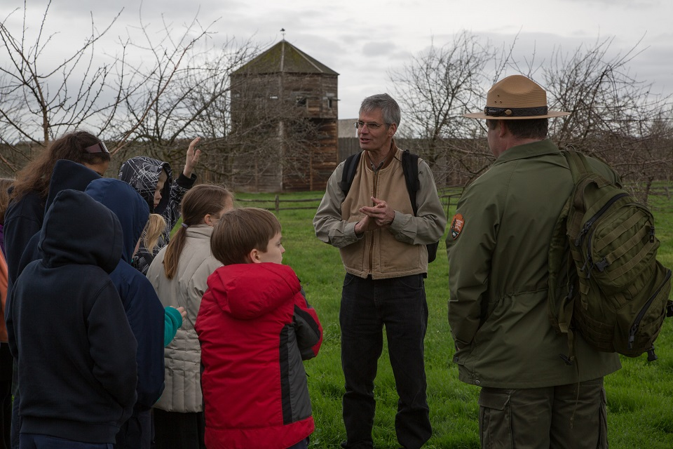 Photo of man standing near Fort Vancouver with park ranger and group of children.