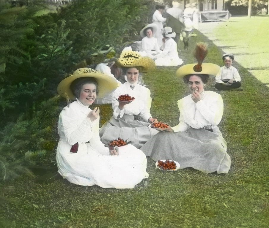 Historic lantern slide image of women wearing light colored dresses and straw hats sitting on lawn eating berries.