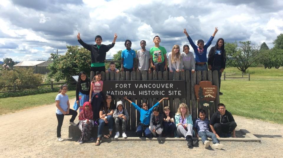Students and teachers sit and stand around the entrance sign at Fort Vancouver