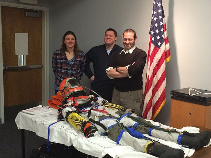 Photo of PSU Anthropology Professor Dr. Cameron Smith poses with his build team and his home built pressure flight suit he intends to conduct high altitude tests with this year.