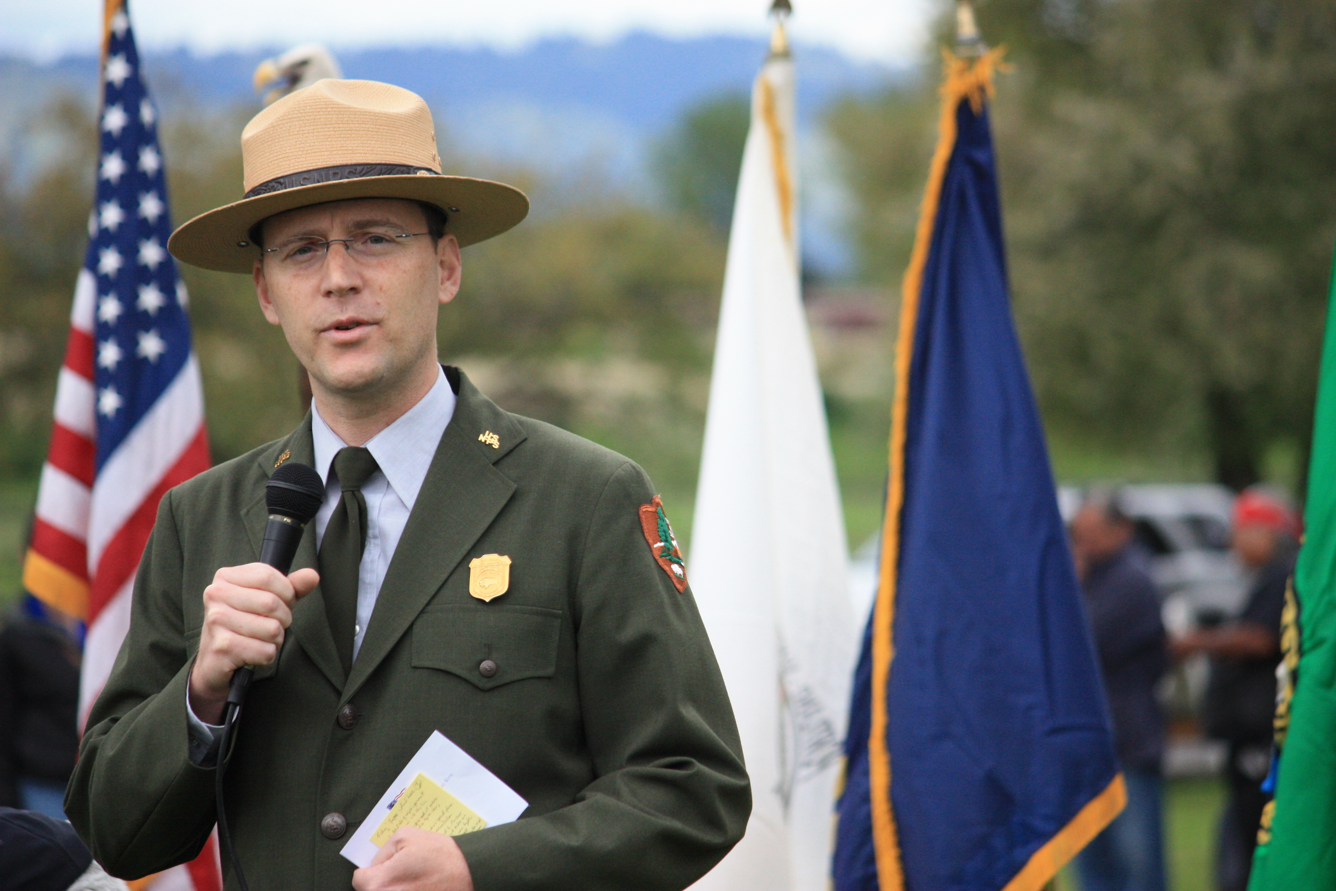 Photo of Greg Shine in park ranger uniform speaking to the crowd at the Nez Perce Chief red Heart Reconciliation Event in 2013