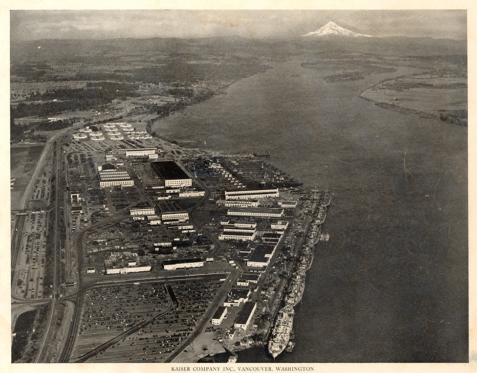 Aerial photograph of the Vancouver Kaiser Shipyards on the Columbia River. Six Navy ships are docked. Mount Hood is visible in the background.