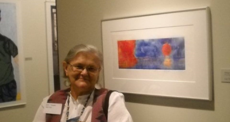 Artist Lois Thadei poses with painting