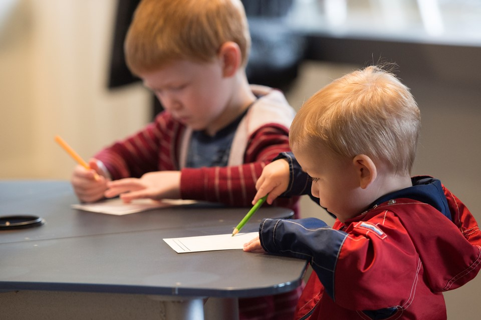 Photo of two young children coloring at a table.