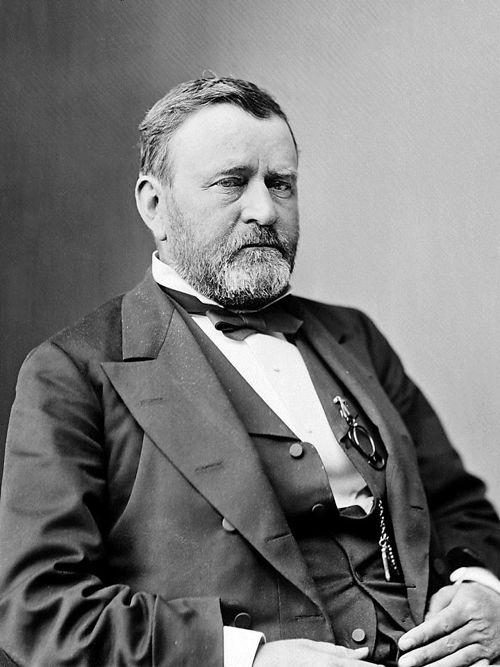 Three-quarters length photograph of seated man.