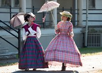 Two women in historic costume walk through Vancouver Barracks