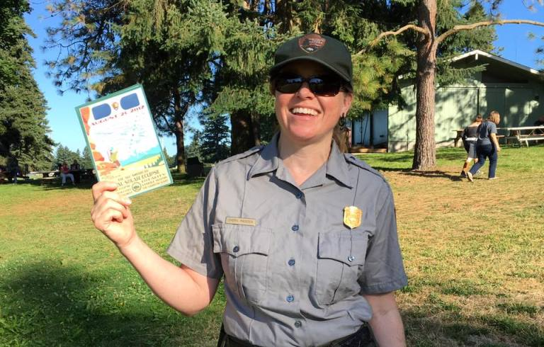 Park ranger holding eclipse glasses at Fort Vancouver National Historic Site