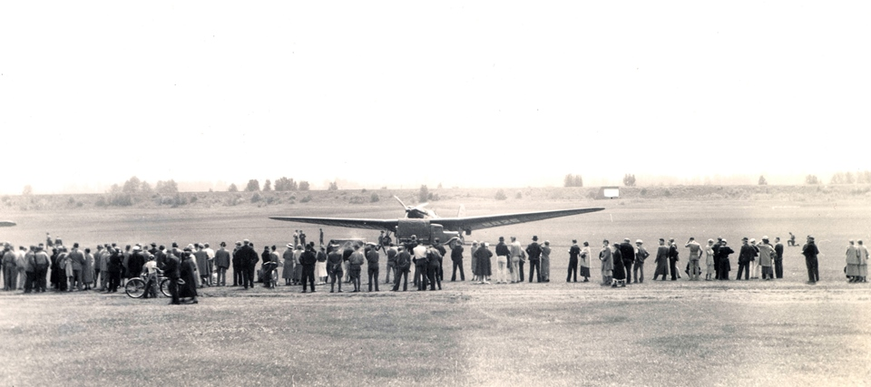 ANT-25 aircraft sits in field surrounded by onlookers