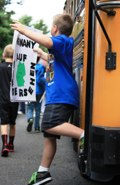 A third grade student disembarks the bus en route to the Children's Cultural Parade.