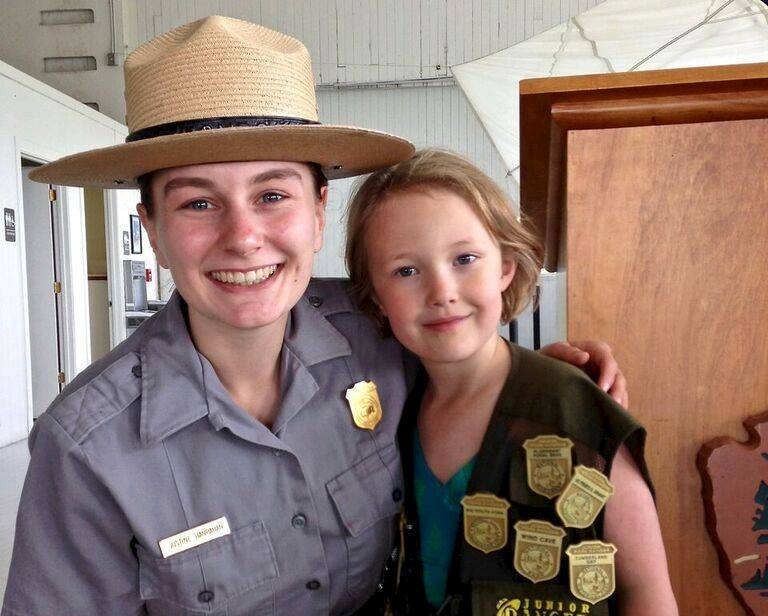 National Park Ranger posing with Junior Ranger wearing badges from many parks
