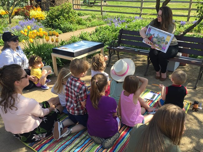 Photo of children sitting in a garden listening to an adult reading a picture book.