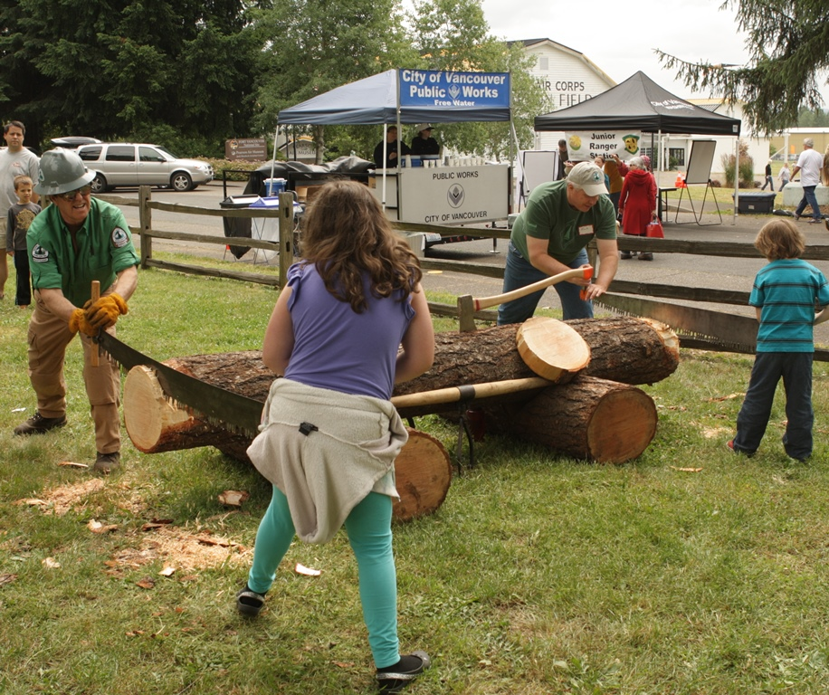 Sawyers and children work together to saw a log at Get Outdoors Day