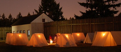 Tents glow in the evening of an 1840s Overnighter