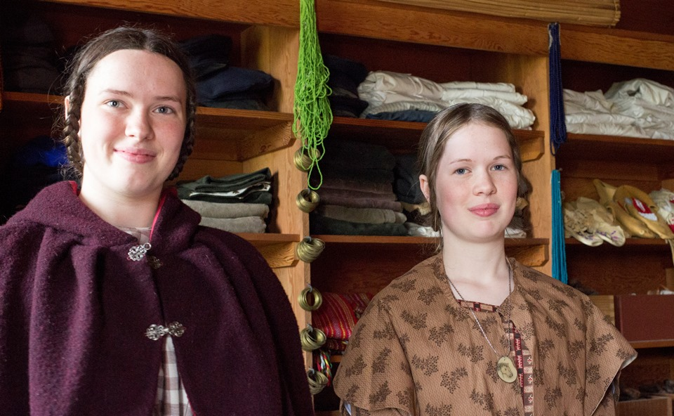 Two female volunteers dressed in 1840s costumes
