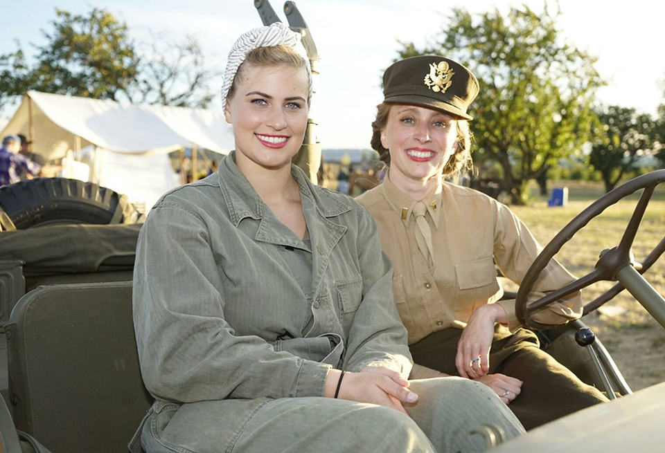 Photo of two women - one dressed as a Rosie the Riveter, one dressed in a military uniform - sitting in a World War II period jeep.