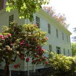 Photo of the exterior of the McLoughlin House with a red rhodedendron in the foreground.