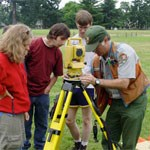 Archaeologist instructing students in the operation of surveyorr's equipment