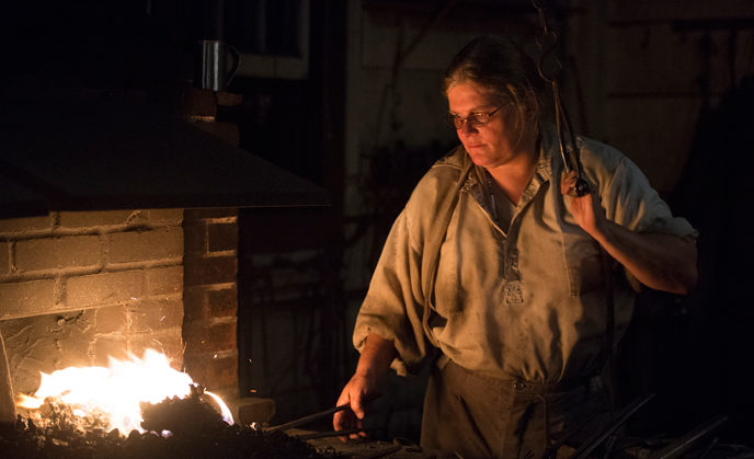 A blacksmith shop volunteer in 1840s costume works a hot forge during a nighttime special event.